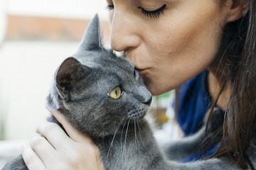Woman kissing Russian Blue