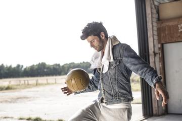 Portrait of man kicking football