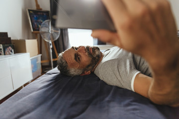 Serious looking man lying on his bed taking a selfie with his smartphone