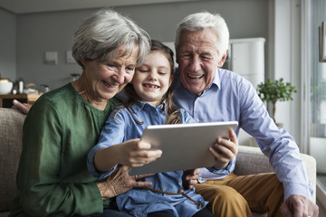 Grandparents and their granddaughter sitting together on the couch looking at digital tablet