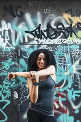 Portrait of smiling young woman standing in front of graffiti wall