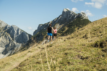 Austria, Tyrol, Tannheim Valley, young couple jogging in mountains