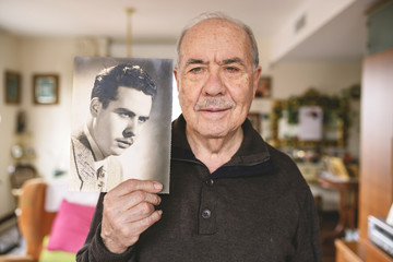 Portrait of senior man showing an old picture of himself