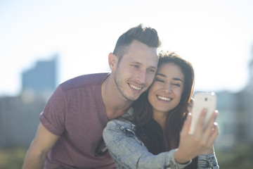 Portrait of happy young couple taking a selfie with smartphone