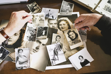 Hands of senior couple holding old photographies of themselves