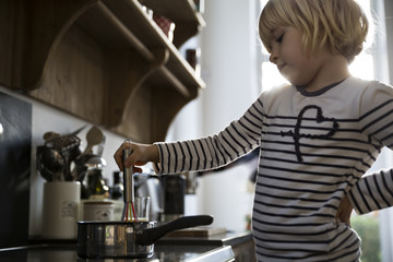 Girl in kitchen cooking with saucepan