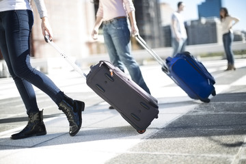 Friends on city trip with rolling suitcases