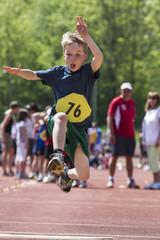 Germany, Munich, Boy longjumping on sports meeting