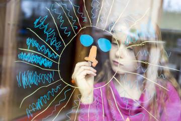 Girl painting sun on windowpane