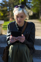 Portrait of blond woman reading an ebook