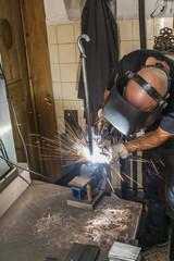 Knife maker welding in workshop at work