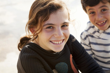 Spain, Barcelona, portrait of happy girl with brother watching in the background