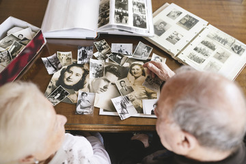 Senior couple with photo albums and old photographies at home