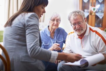 Woman explaining document to senior couple
