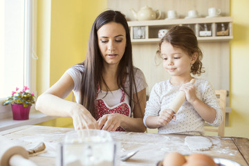 Portrait of mother and her little daughter baking together