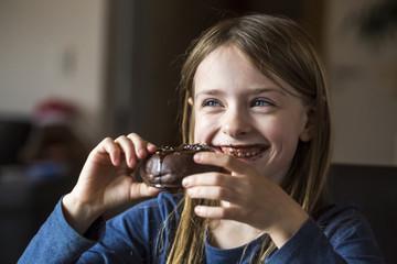 Portrait of smiling girl eating chocolate doughnut