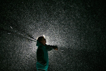 Silhouette of skier on backlit at night. Snowing