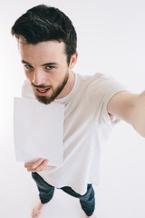 Bearded man holding a blank white sheet of paper