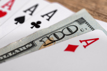 four poker aces with 100 dollar bills