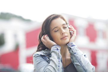 Portrait of young woman with closed eyes listening music with headphones