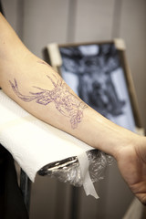 Forearm with stenciled tattoo in a tattoo studio