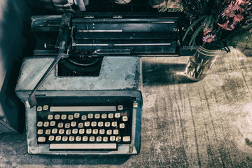 Retro old vintage typewriter with a vase of flowers with color e