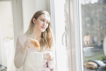 Portrait of young woman with croissant and cup of coffee looking through window
