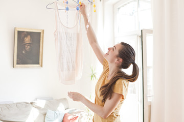 Young woman hanging up a top in her living room
