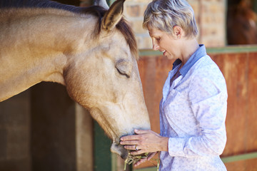 Woman feeding horse with straw