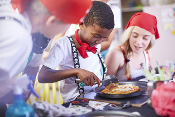 Children dressed up as pirates cutting pizza with a pizza cutter