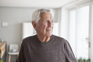 Portrait of pensive senior man at home