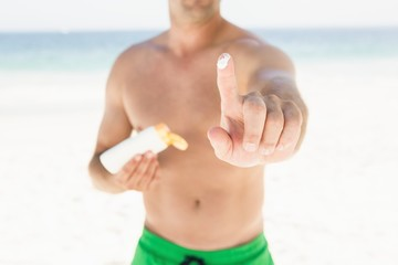 Portrait of man applying sun cream