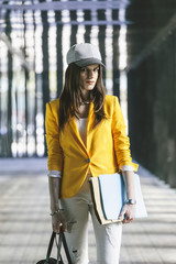 Spain,Catalunya, Barcelona, young modern businesswoman with yellow jacket on the move