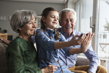 Little girl taking selfie with her grandparents at home
