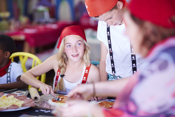 Children dressed up as pirates preparing pizza on a party