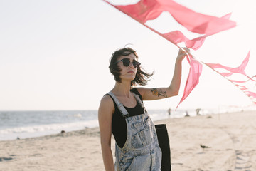 USA, New York, Coney Island, young woman holding red flags on the beach