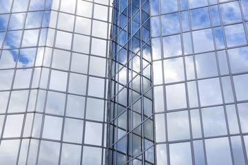 glass office facade reflects clouds and blue sky
