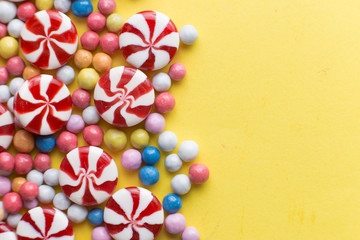 Candies colorful mix on yellow bright background with copy space top view.