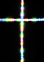 Cross made with several light colors with black background