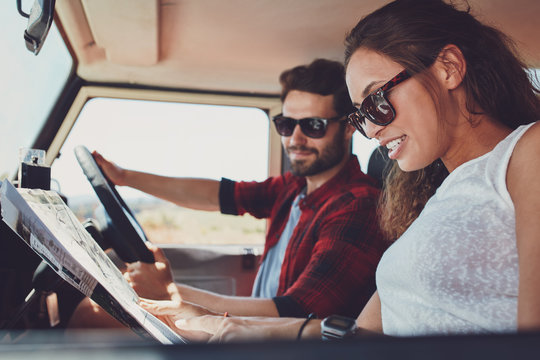 Young couple on roadtrip reading map for directions