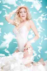 Blonde sensual girl over feathers.