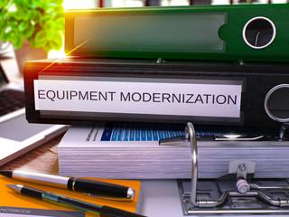 Black Office Folder with Inscription Equipment Modernization on Office Desktop with Office Supplies and Modern Laptop. Equipment Modernization Business Concept on Blurred Background. 3D Render.
