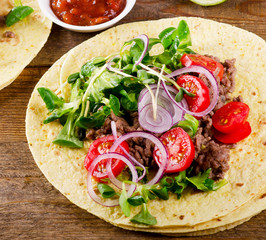 Two mexican tacos on a wooden table.
