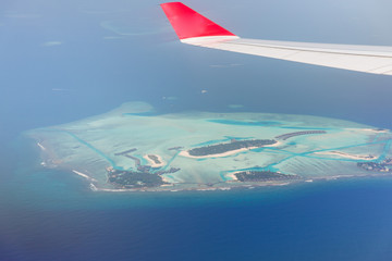 close up of airplane wing above island in ocean