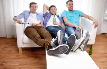 close up of male friends watching tv at home