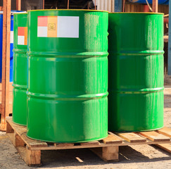 Green barrels with label on wooden pallets