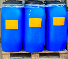 Scratched blue packed barrels with orange labels
