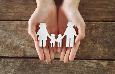 Female hands holding family figure on wooden  background