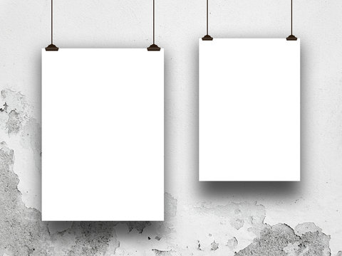 Close-up of two blank frames hanged by clips against grey stained concrete wall background