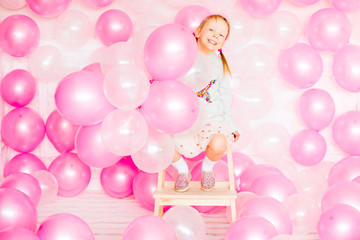 little girl playing with pink balloons